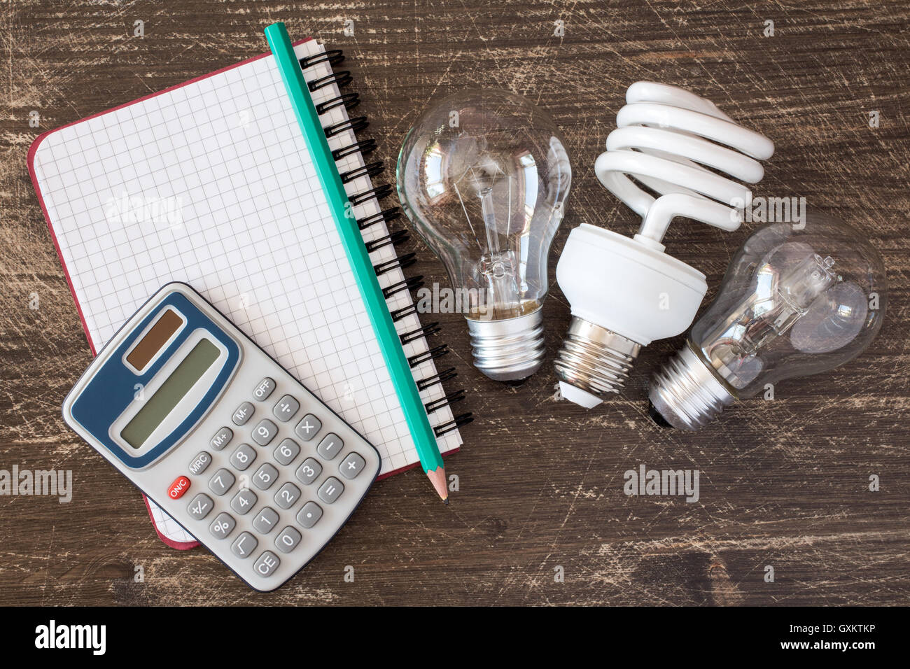 Three different light bulbs and notebook with digital calculator - Stock Image