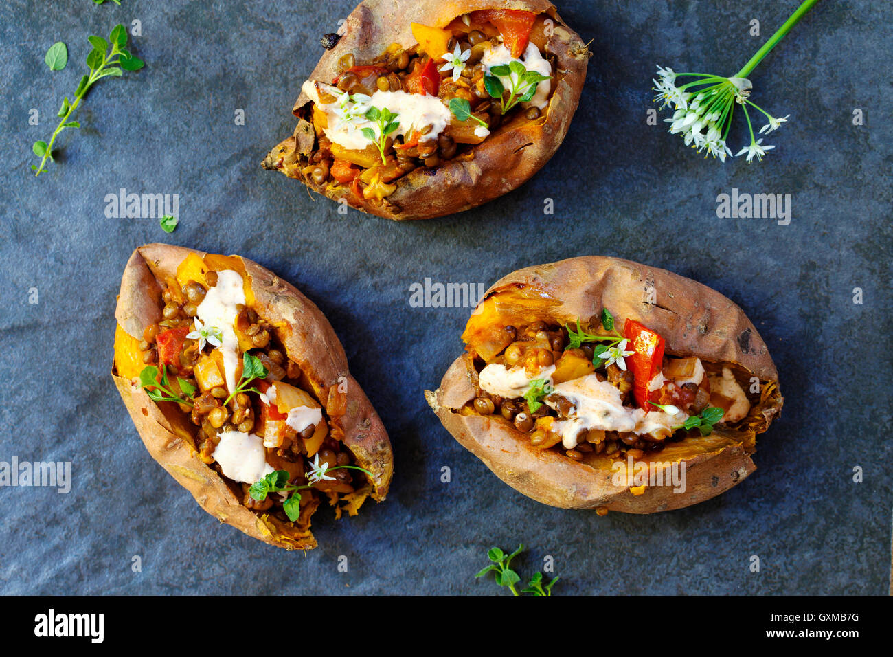 Sweet potatoes with spicy lentils, yellow pepper and tomato filling, thyme, garlic flowers and chipotle sour cream - Stock Image