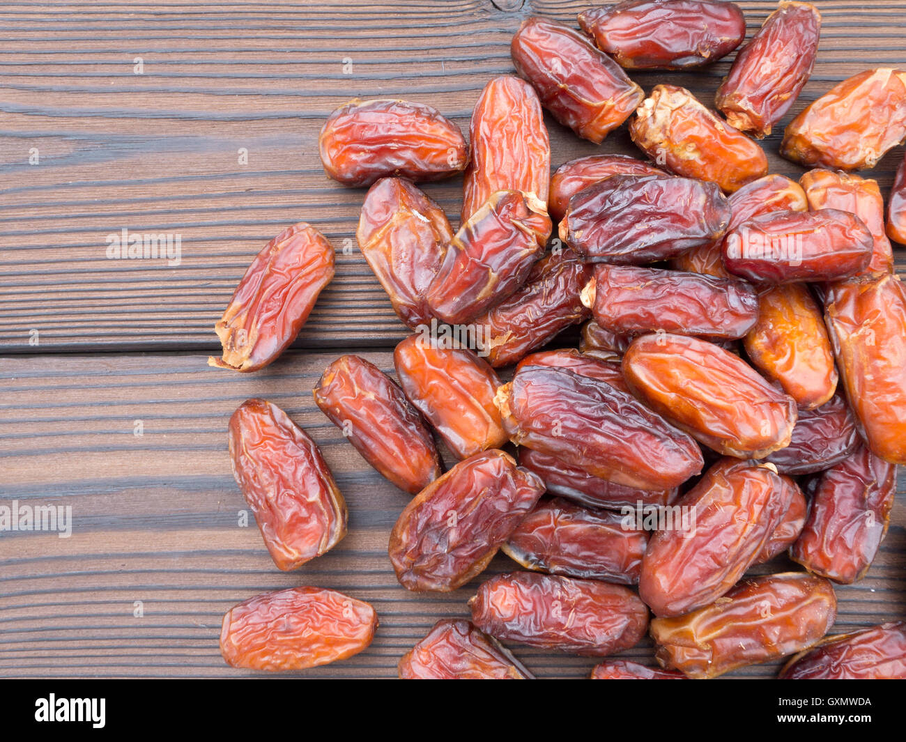Dried dates on the dark textured wooden planks - Stock Image