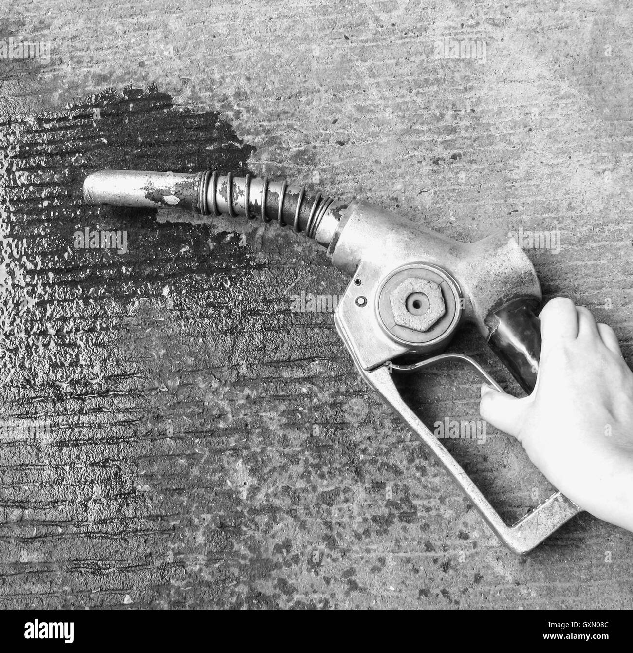 Hand holding old gas pump, oil wasting on the ground.(Black and white effect) - Stock Image
