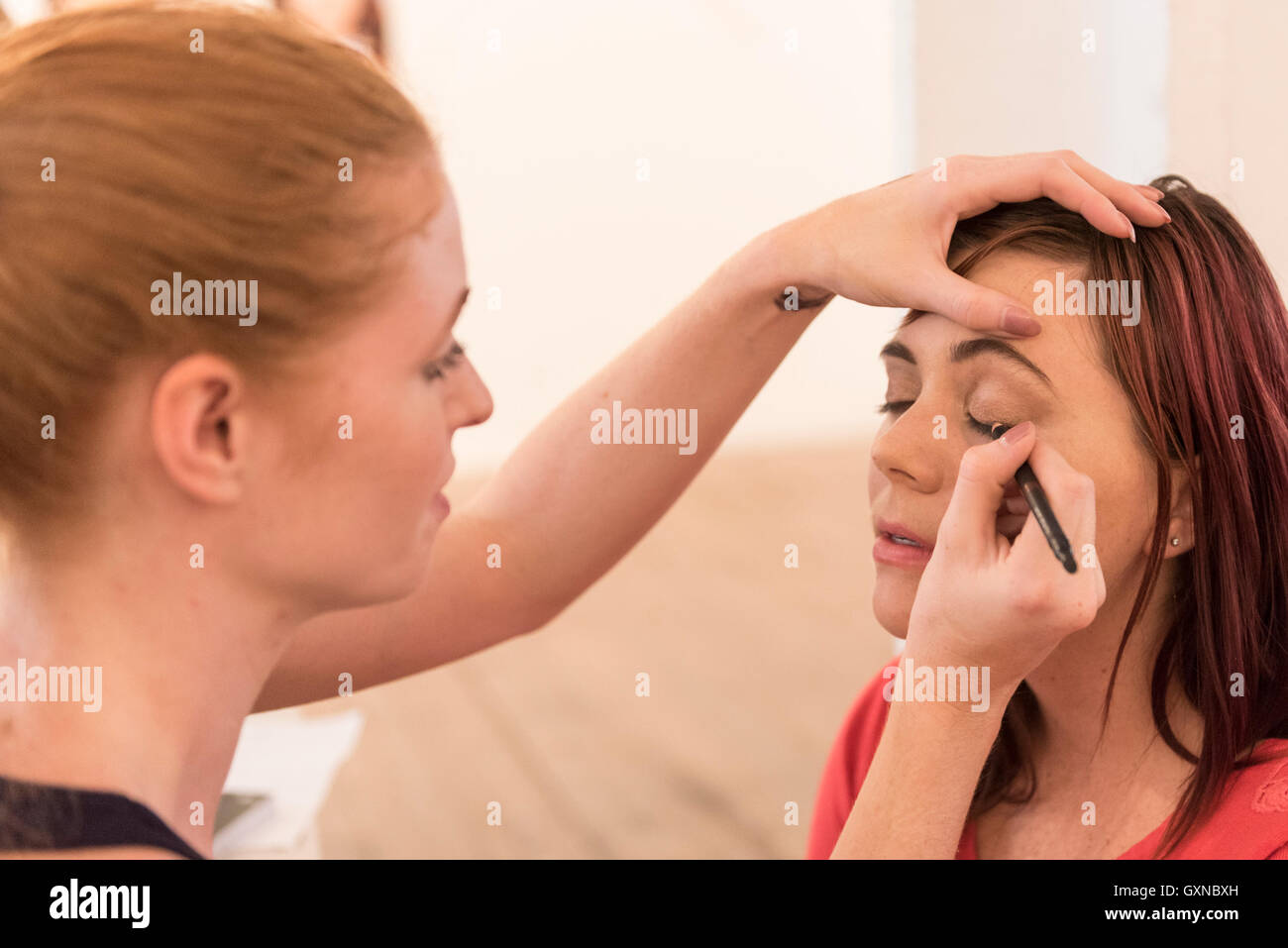 London, UK. 17th September, 2016.   A woman has make-up applied. Ginger, auburn and redheaded people gathered in - Stock Image