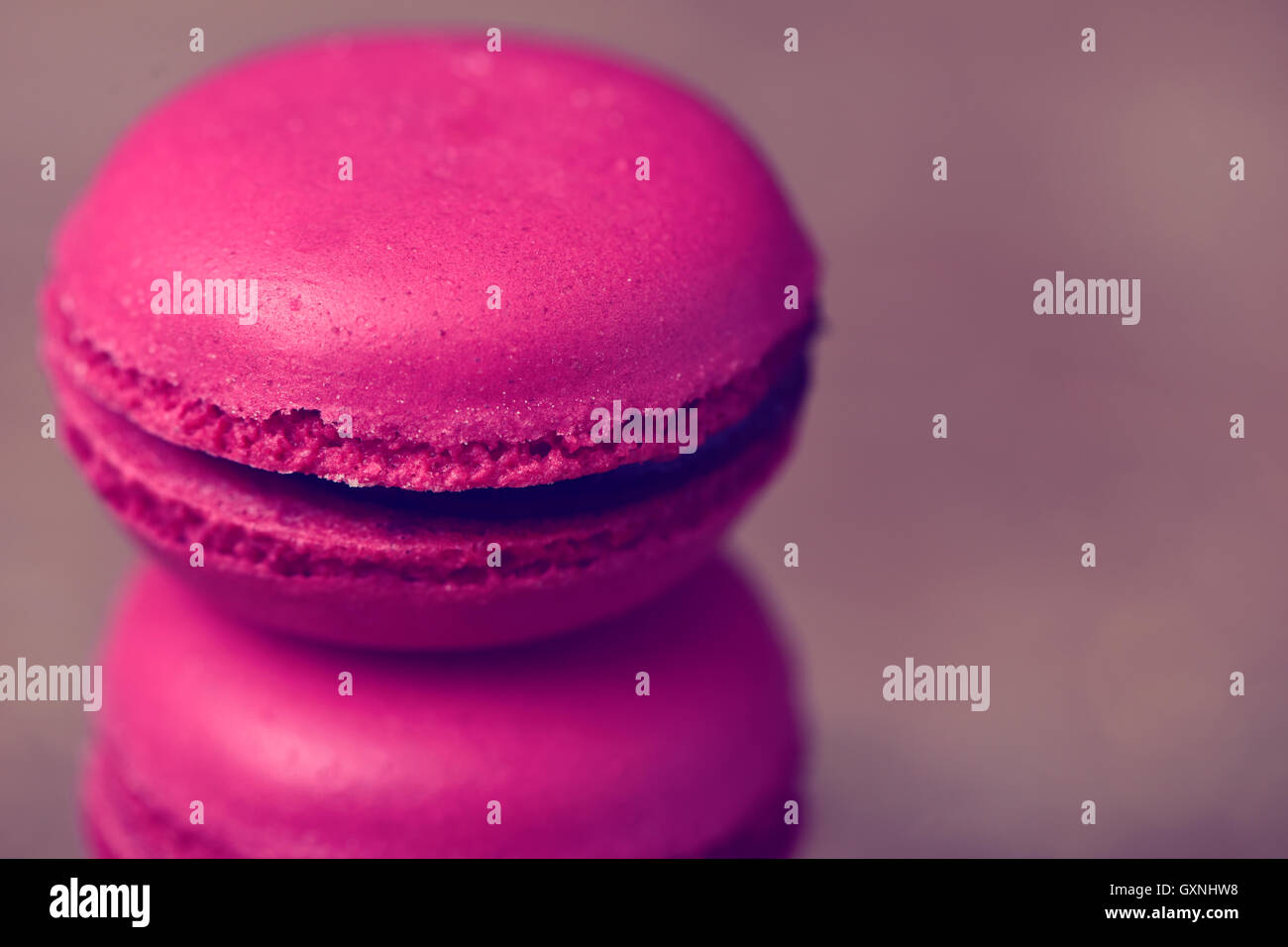closeup of a stack of appetizing purple macarons against a gray background - Stock Image