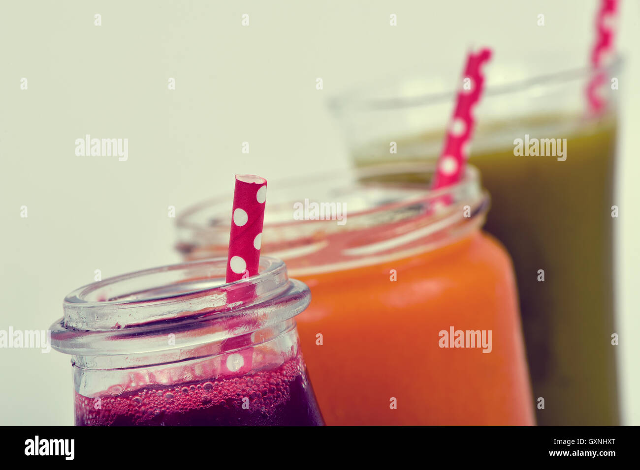 closeup of three different fresh smoothies served in a glass, a glass jar and a glass bottle with red drinking straws Stock Photo
