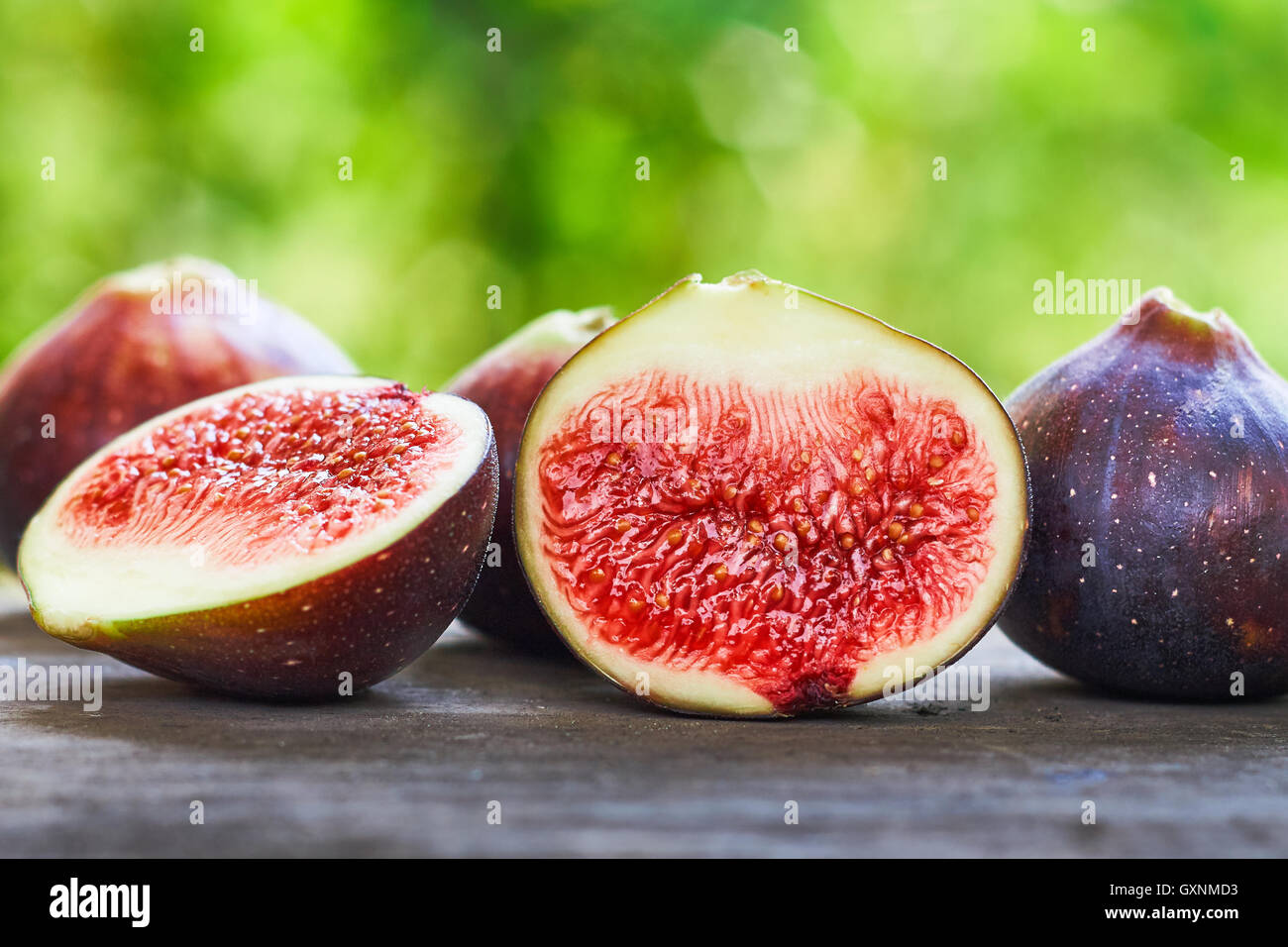 Fresh ripe black figs on rustic grey wooden table with green blurry background. Copy space - Stock Image