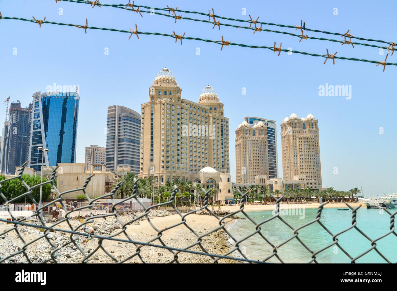 Fences and barbed wire in front of the skyscrapers of Doha, Qatar - Stock Image