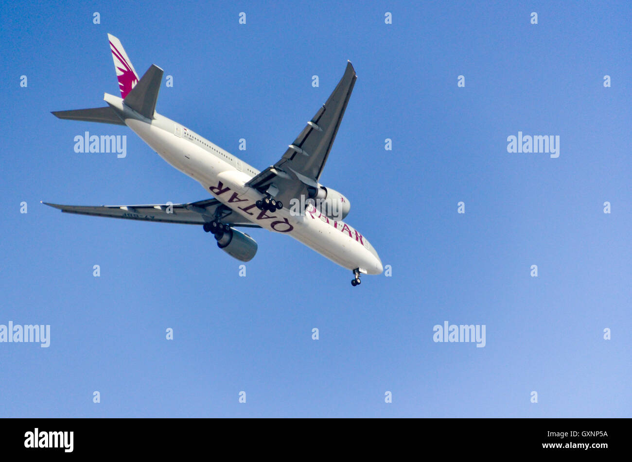 Boeing aircraft of Qatar Airways (Boeing 777-2DZ(LR)) in the blue sky of Doha - Stock Image