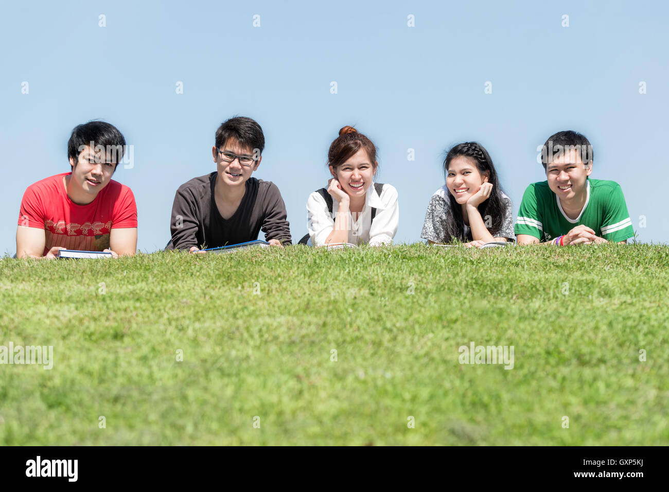 Group of friends studying outdoors in park at school.Five Asian high school student lying in grass at school. - Stock Image