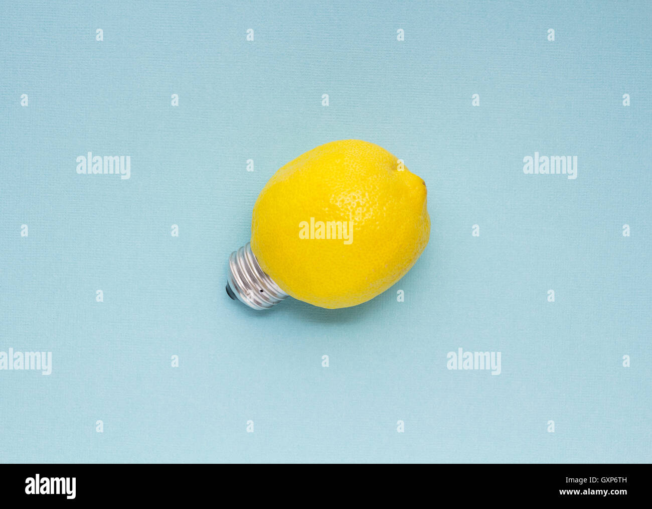 Creative concept photo of a lemon with a bulb on blue background. - Stock Image