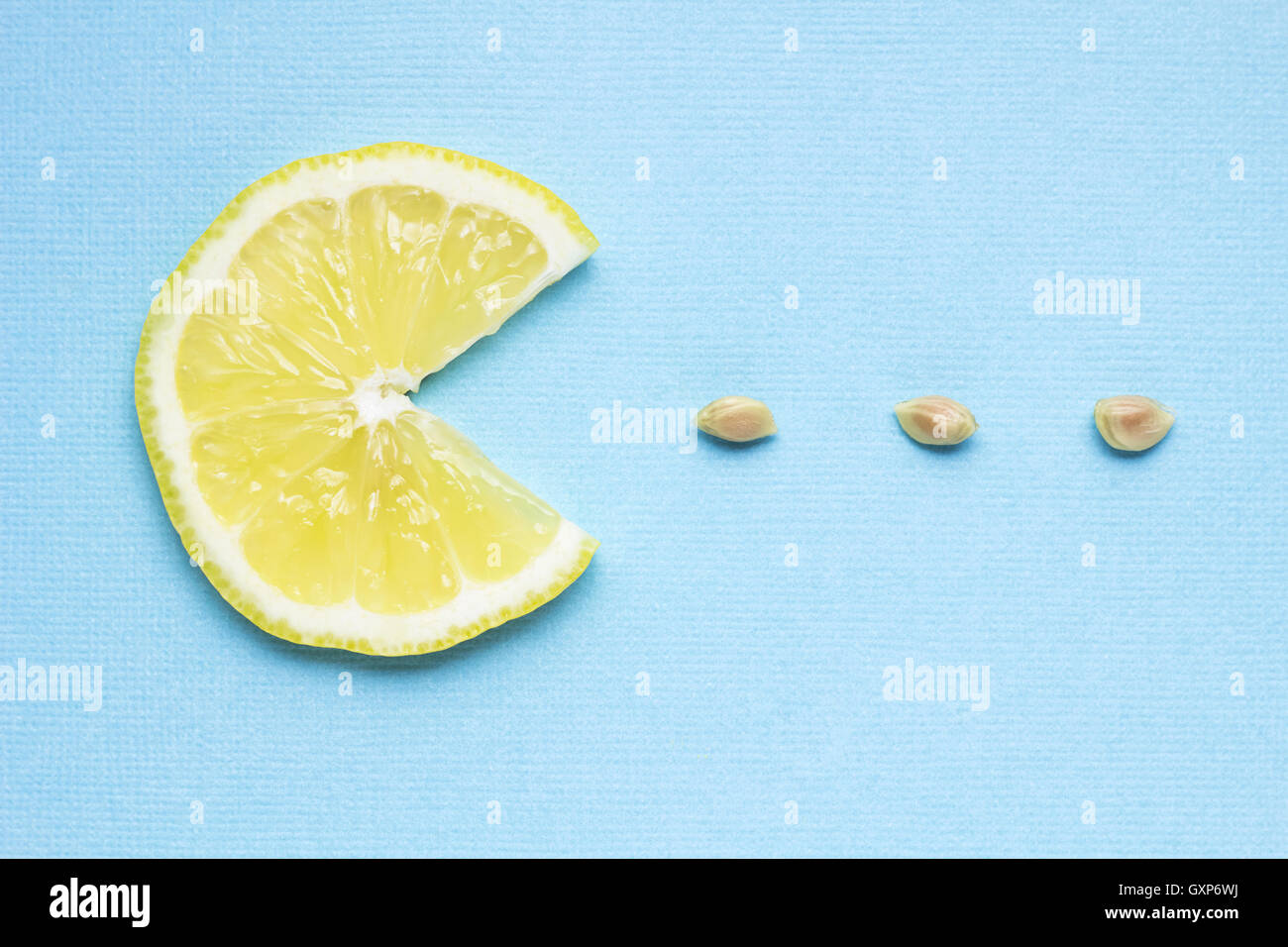 Creative concept photo of a lemon slice eating seeds on blue background. - Stock Image
