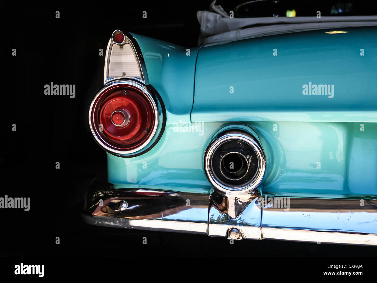 Chrome rear tail lights, bumper and exhaust of convertable turquoise vintage car. - Stock Image