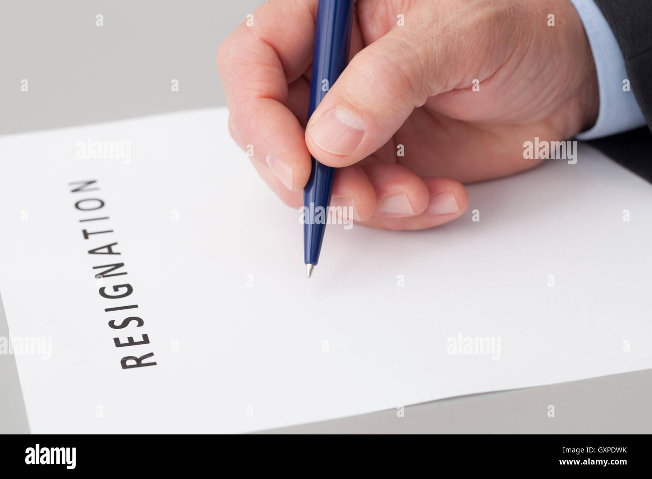 Man with a pen in the hand, writing a letter of resignation on a table - Stock Image
