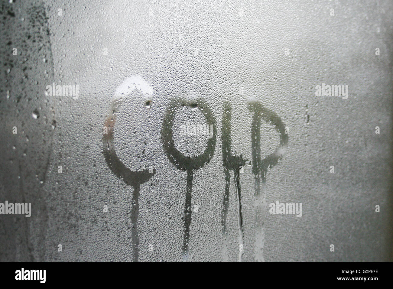 Cold text written in condensation on glass window pane. - Stock Image
