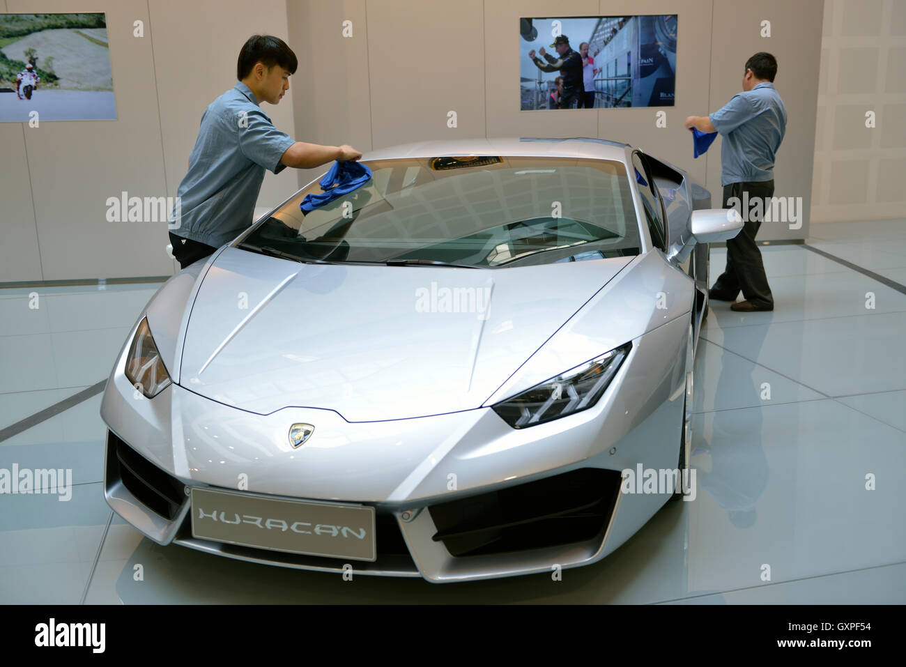 Chinese man cleans a Lamborghini at a showroom in AUDI China in Beijing, China. 05-Sep-2016 Stock Photo