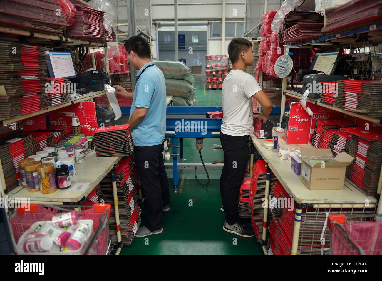 Workers wrap parcels of goods shopped from overseas through Jumei Global online channel during delivery at EHL International - Stock Image