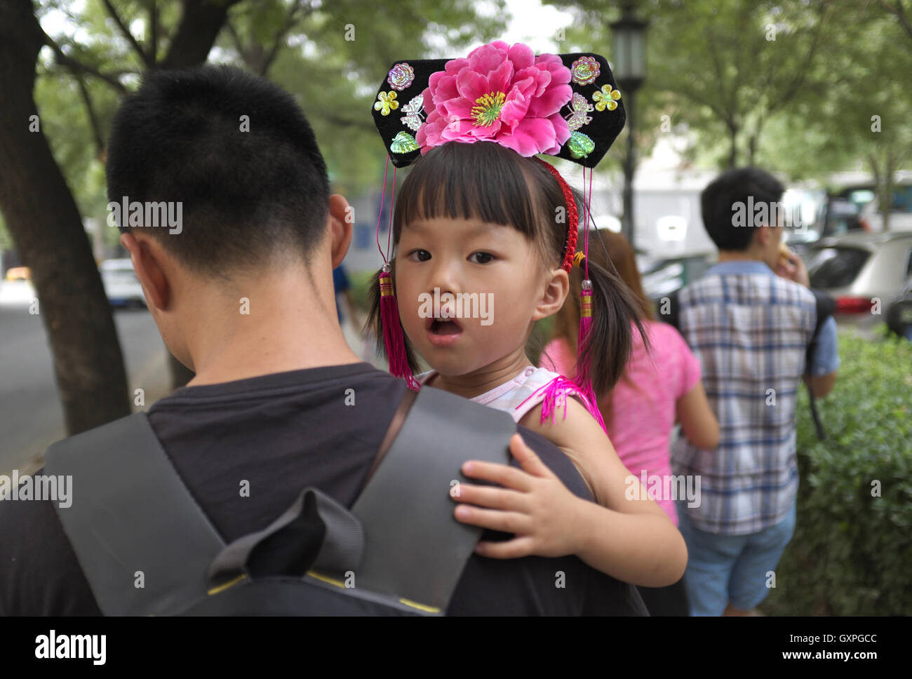 A little Chinese girl wears a hat of Manchu princess in late Qing Dynasty in Beijing, China. 04-Sep-2016 - Stock Image