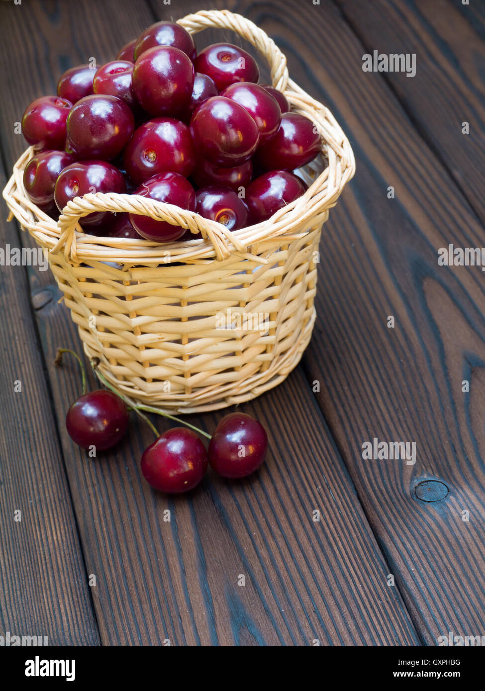 Ripe glossy cherries in the basket on the dark textured wooden planks - Stock Image