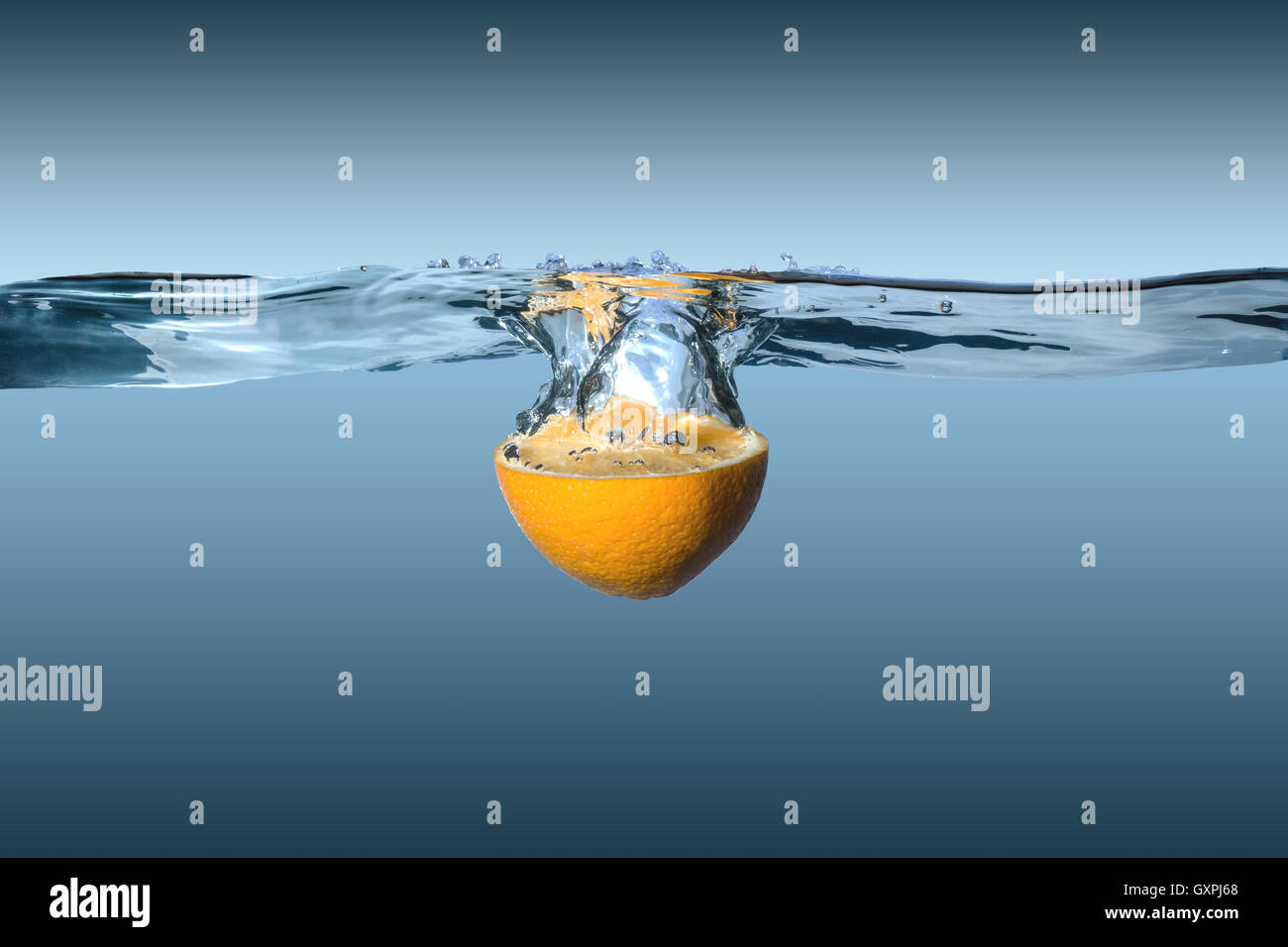 tropical citrus orange fruit in water on a blue background - Stock Image