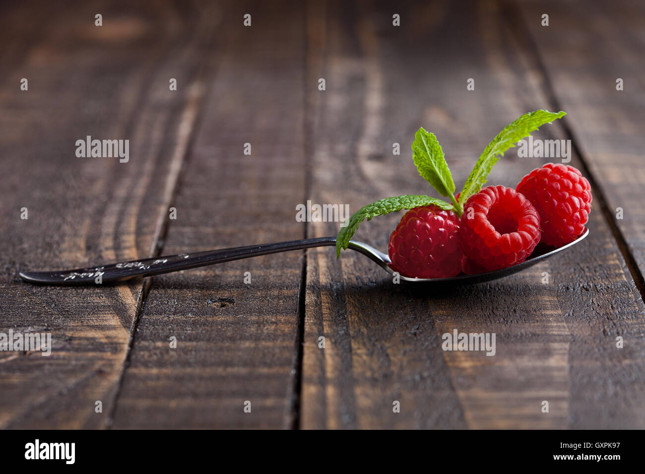 Raspberries on old spoon and mint on grunge wooden board. Natural healthy food. Still life photography - Stock Image