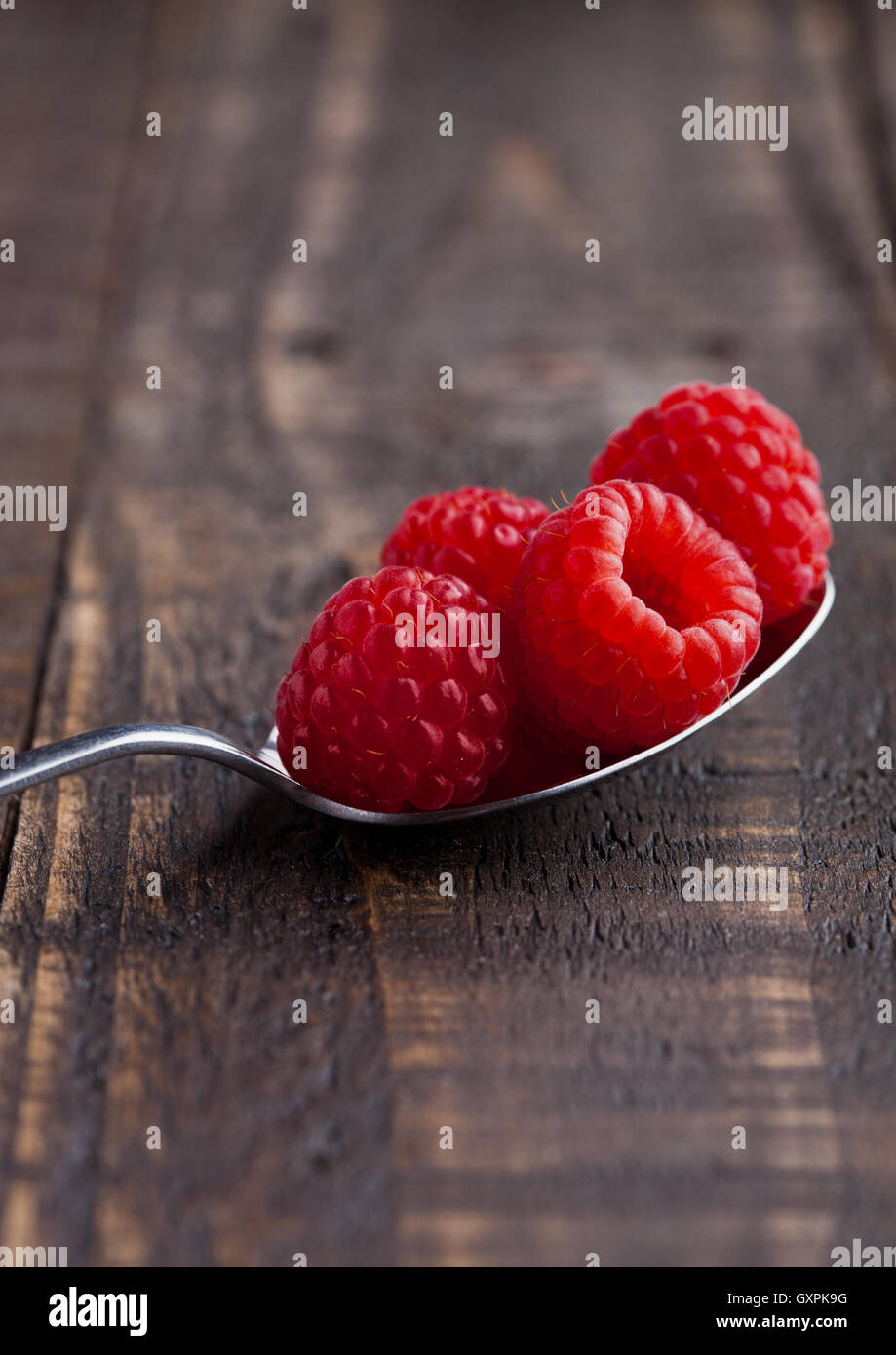 Raspberries on old spoon on grunge wooden board. Natural healthy food. Still life photography - Stock Image