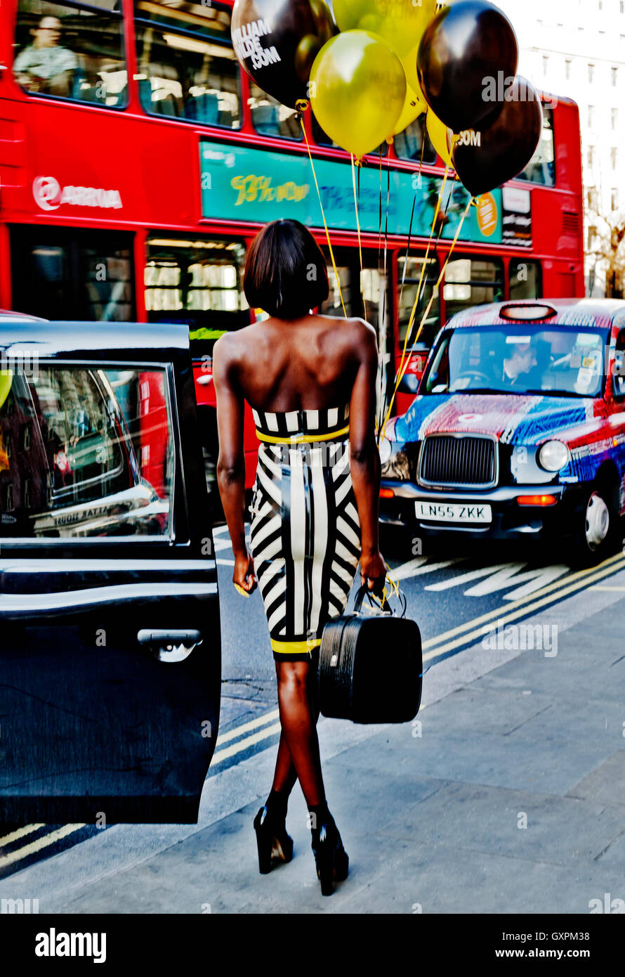 London Fashion Week February 2013, Attractive Fashion Model poses with balloons amidst London traffic, London WC2, - Stock Image