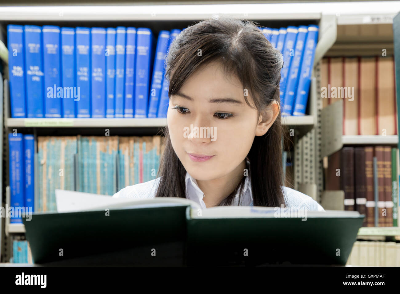 Asian high school student reading in the library at college. One Asian high school student. - Stock Image