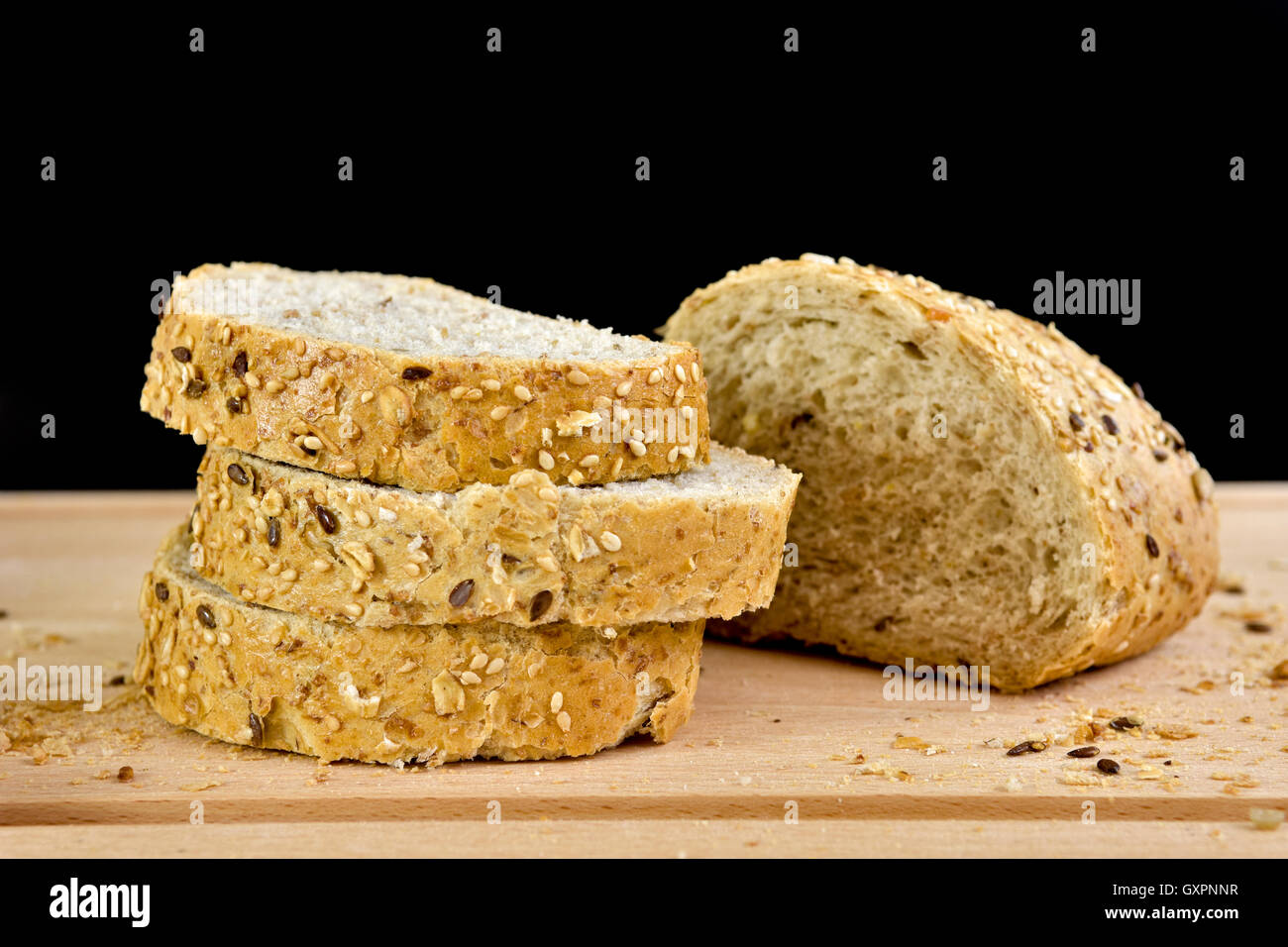 Sliced granary baguette on chopping board, against a black background - Stock Image