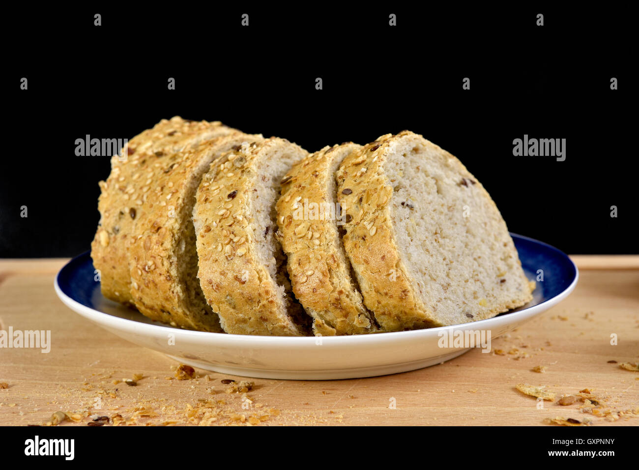 Slices of granary baguette on plate, against a black background - Stock Image