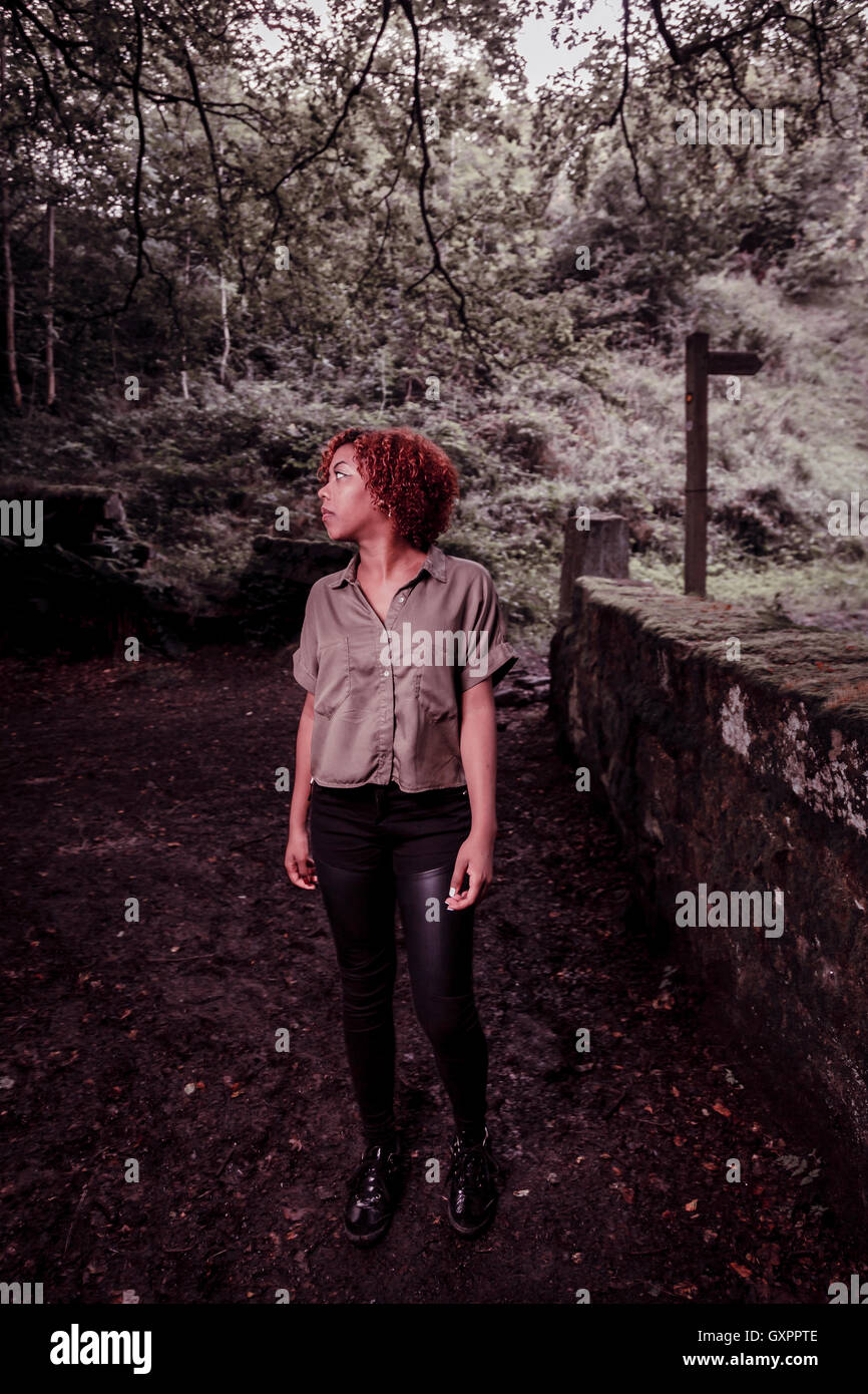 A beautiful black teenager walks in the woods, desaturated colour - Stock Image
