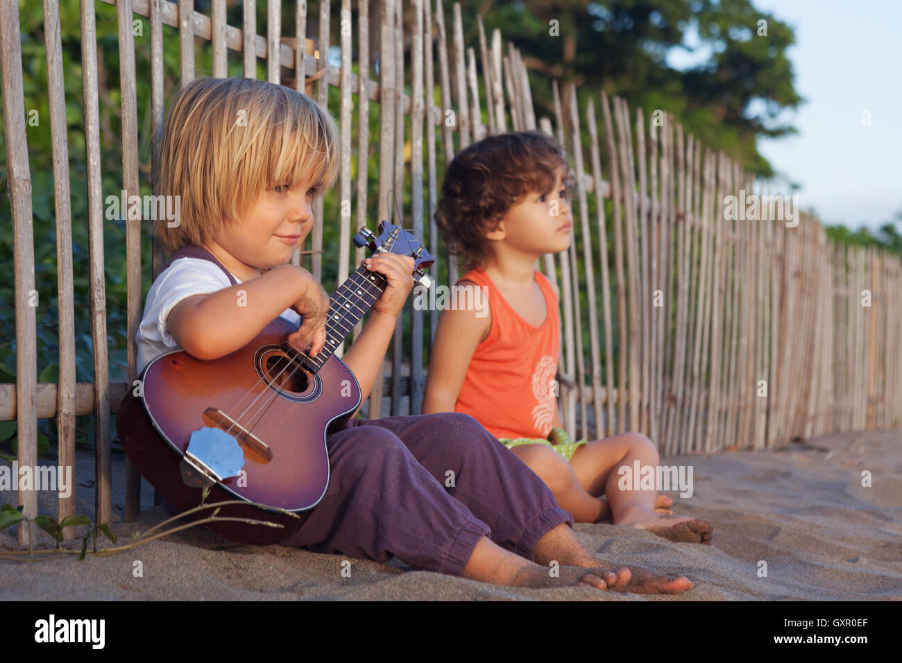Little happy children have fun, play music on Hawaiian guitar ukulele for small baby girl, enjoying sunset ocean - Stock Image
