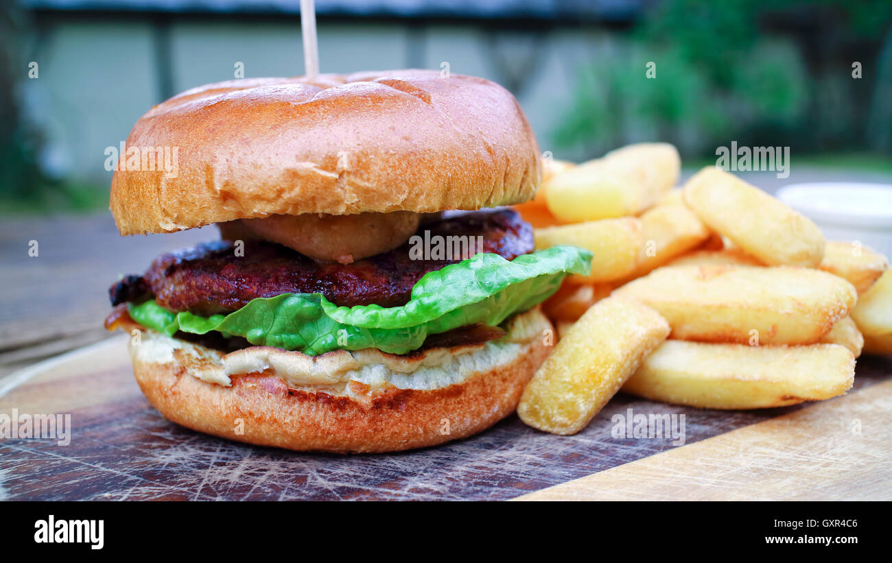 Close up of meat burger with green lettuce, relish in a wheat bun offered on wooden board, accompanied by chunky Stock Photo