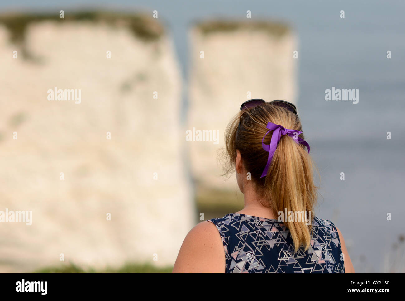 Woman looking out to see over rocks looking pensive with a purple ribbon and pony tail. - Stock Image