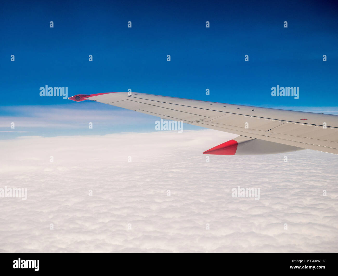 View through plane window with wing and clouds - Stock Image