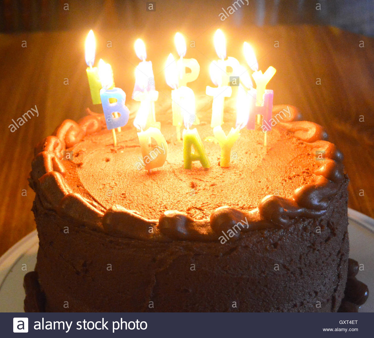 A chocolate birthday cake with lit candles Stock Photo 119773664