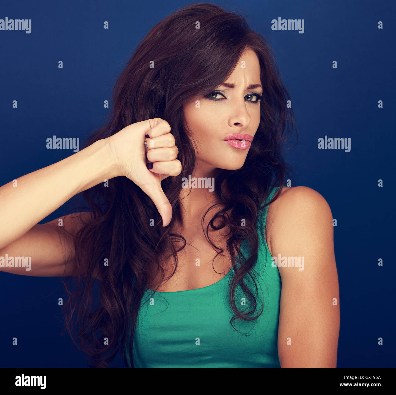 Beautiful grimacing woman with long curly hair showing refuse sign and gesturing thumb down on blue background. - Stock Image