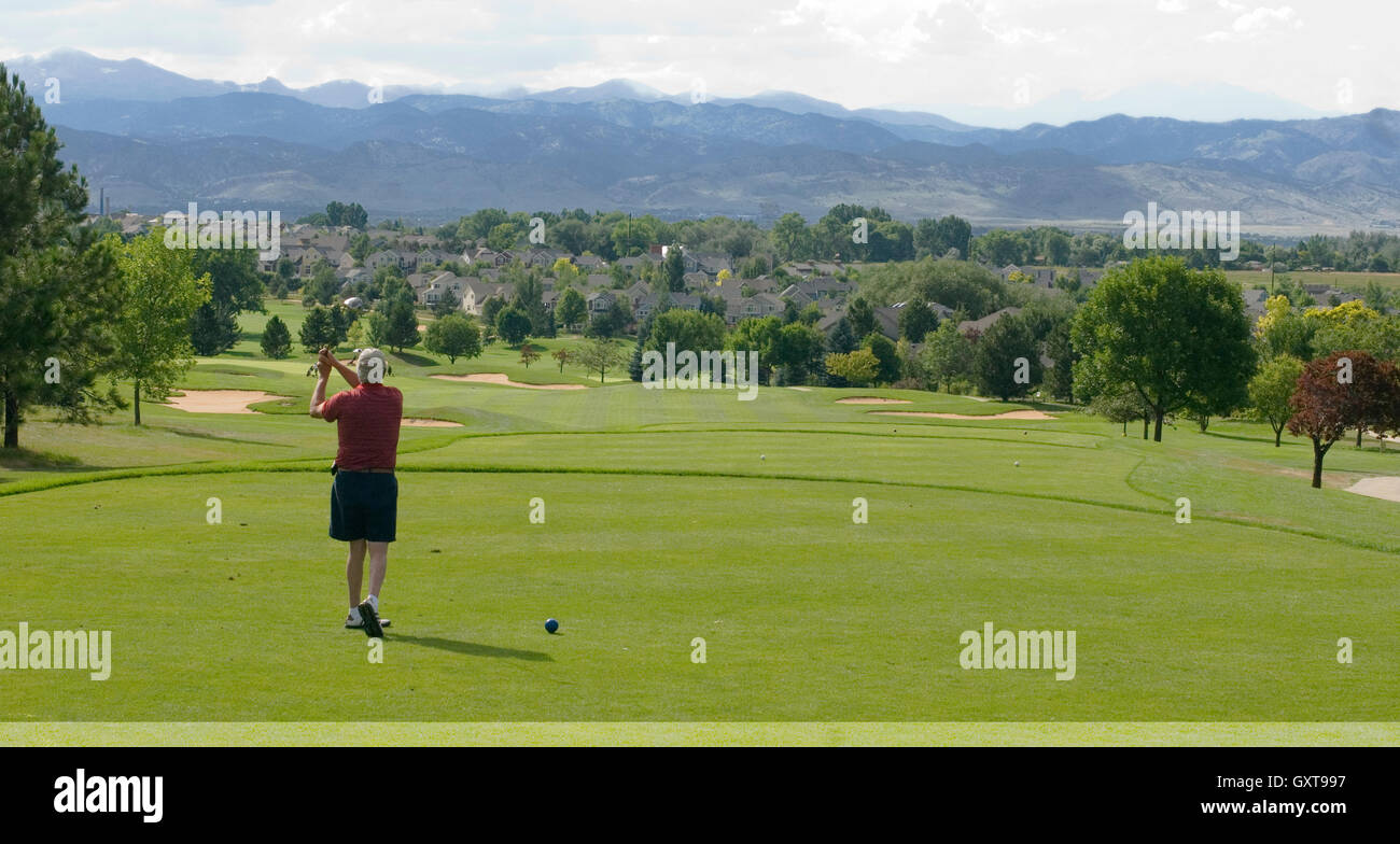 Golfer tees off at 18th hole of Indian Peaks Golf Course - Stock Image