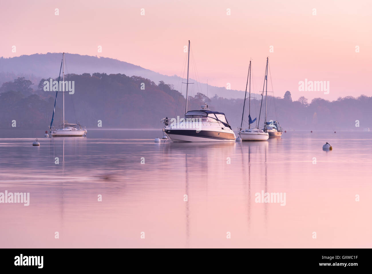 Boats moored on Lake Windermere at sunset, Bowness, Lake District, Cumbria, England. Autumn (November) 2015. - Stock Image