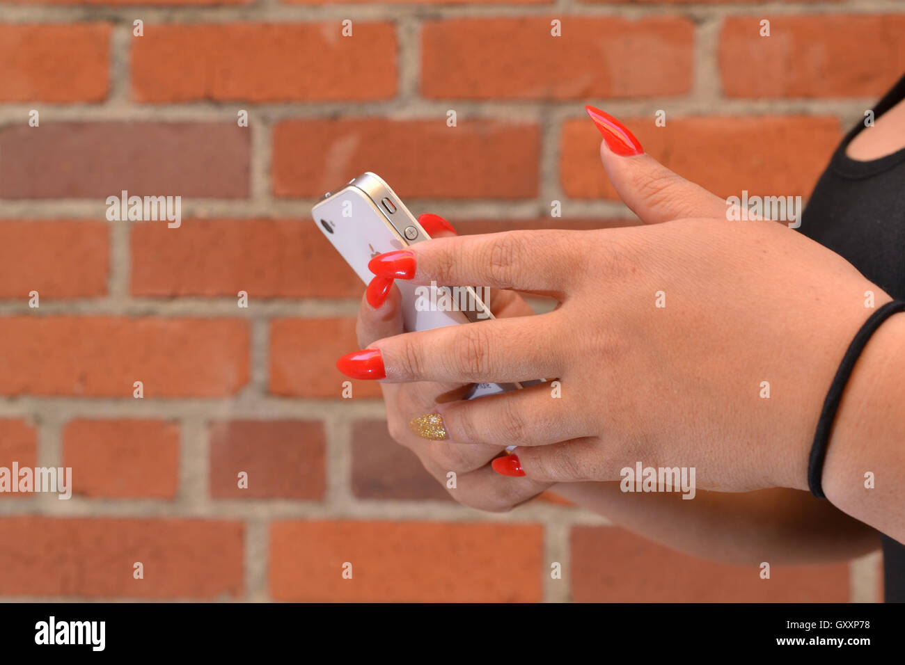 Hands of Hispanic woman checking an iphone, displaying long red ...