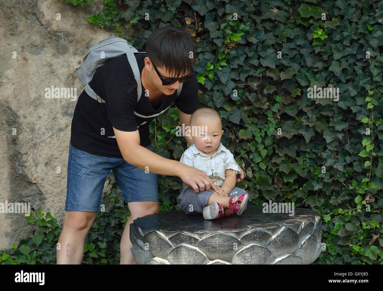 Chinese father teaches his little son to sit in meditation on a lotus throne while visiting Longmen Grottoes - Stock Image