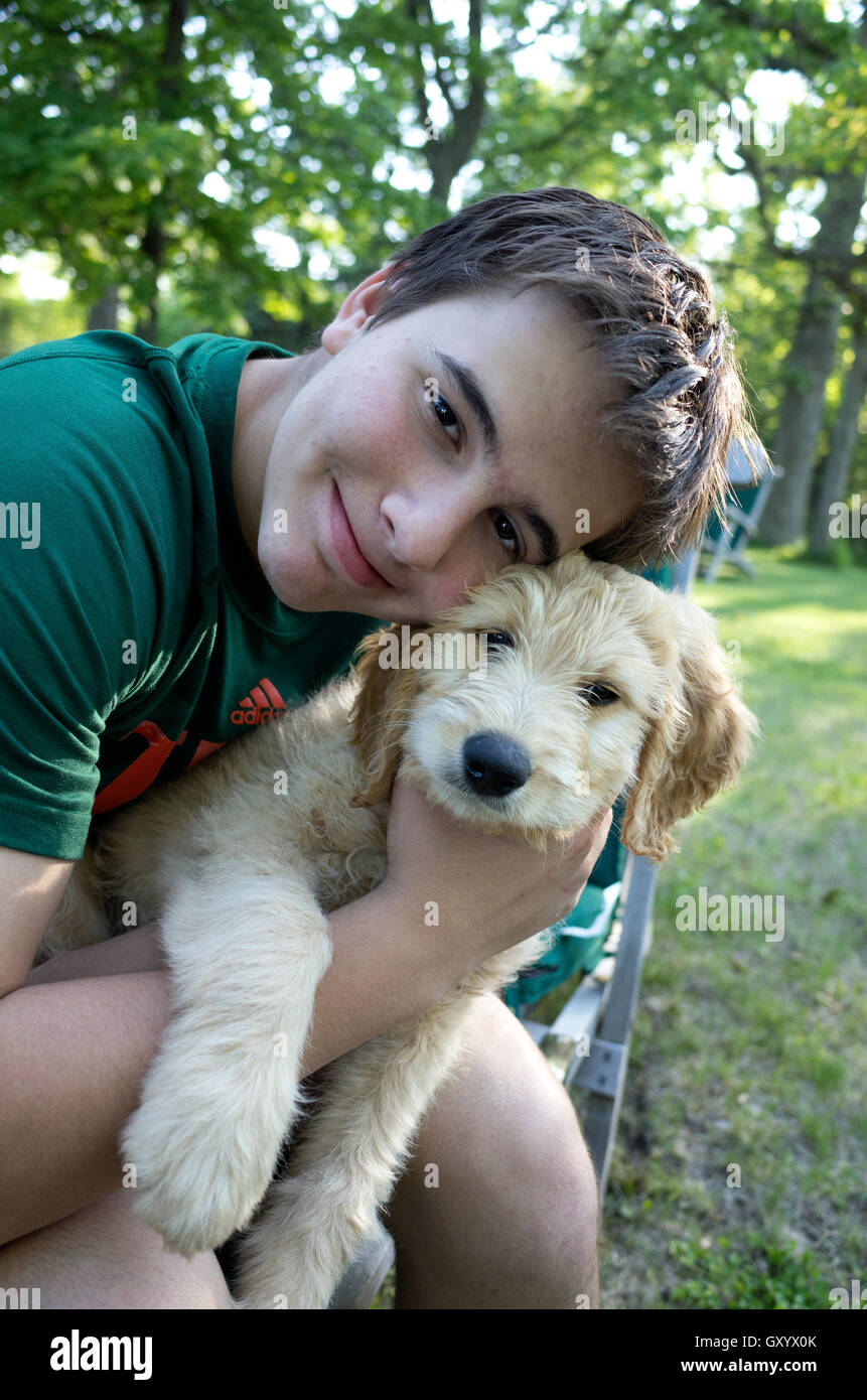 Happy young teen boy embracing Odin his new Goldendoodle puppy. Clitherall Minnesota MN USA - Stock Image