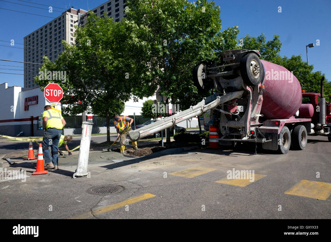 Rotating truck delivers cement to workers for new sidewalk. St Paul Minnesota MN USA - Stock Image