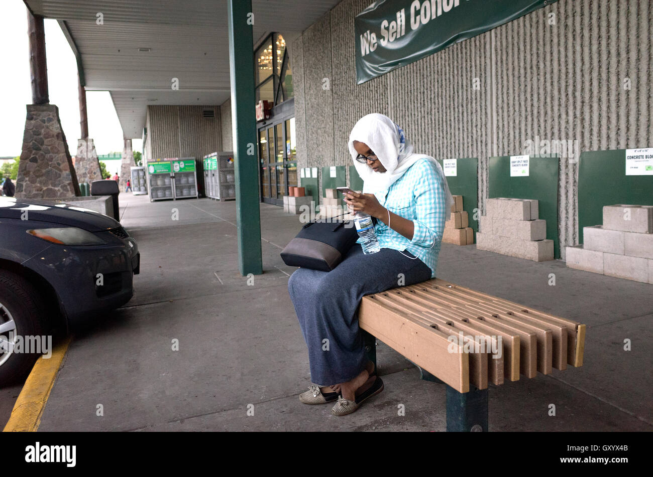 Muslim woman wearing a hijab working her cell phone on a