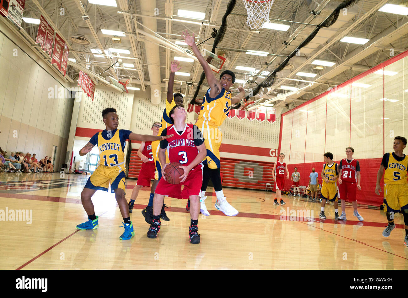 Black teen leaps to block shot in an exciting basketball game. North High School, White Bear Lake Minnesota MN USA - Stock Image