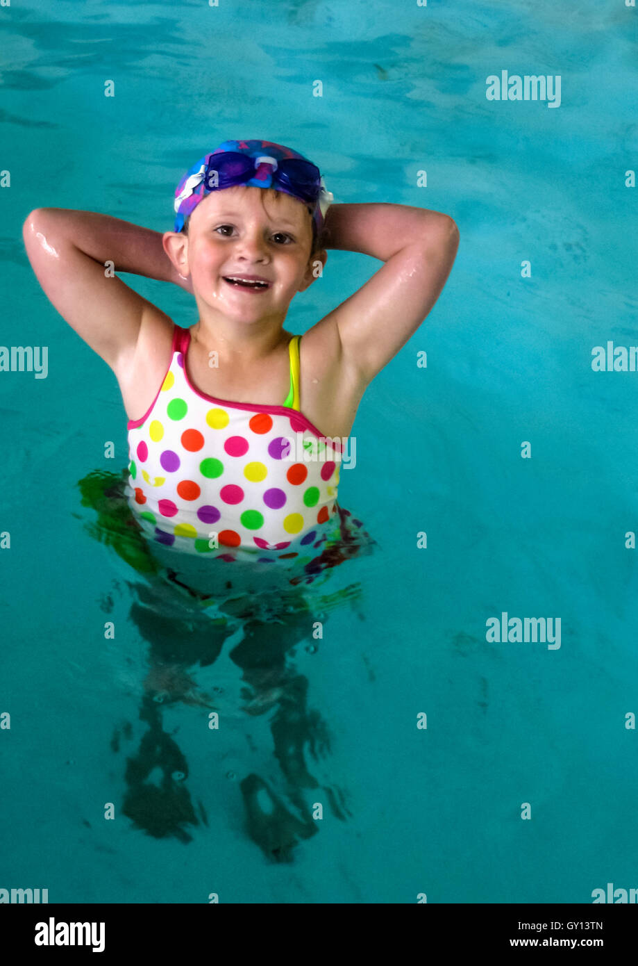 Happy young girl learning to swim at her local pool - Stock Image