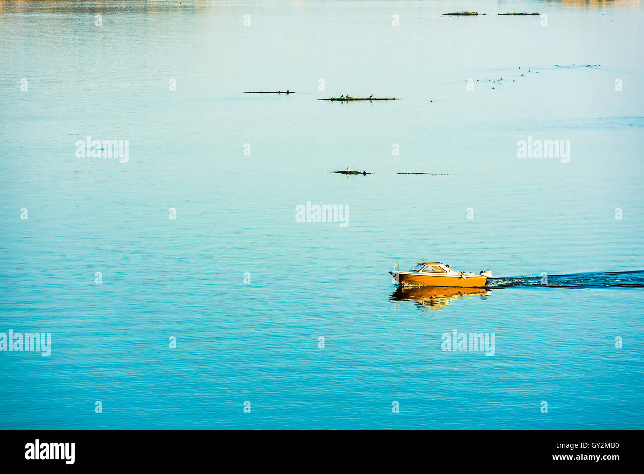 Small motorboat moving slowly through windless sea in the archipelago. - Stock Image
