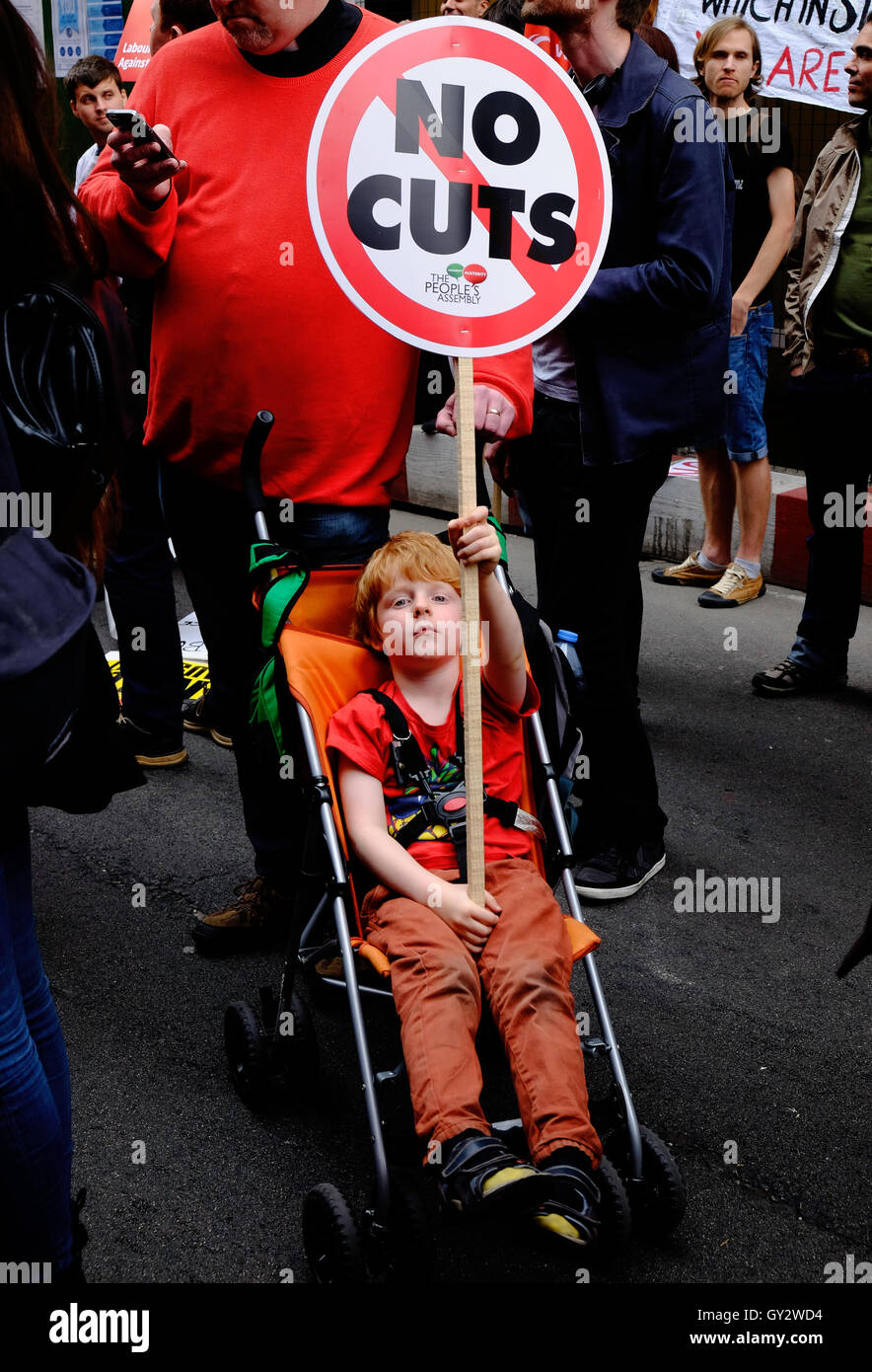 Young, red headed boy in a pushchair waves an anti-austerity placard at a protest in London  as his father checks - Stock Image