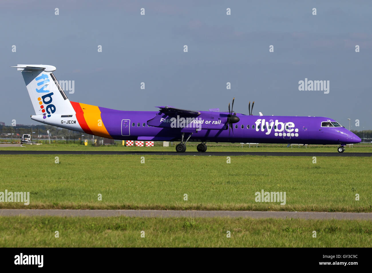 FlyBe DeHavilland Dash-8 touches down on runway 18R at Amsterdam Schipol airport. - Stock Image