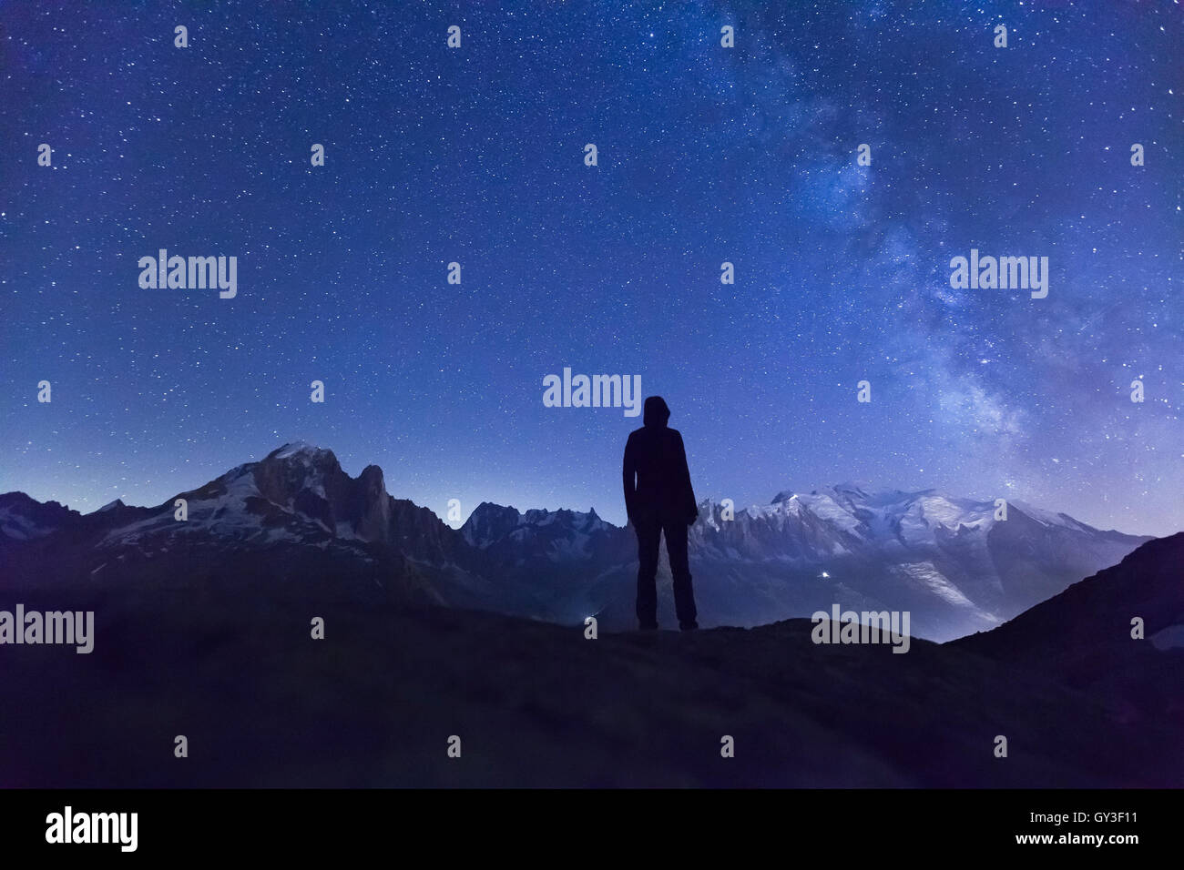 Person watching the stars and the Milky Way in the night sky above the Alps mountain range and the White Mount near - Stock Image