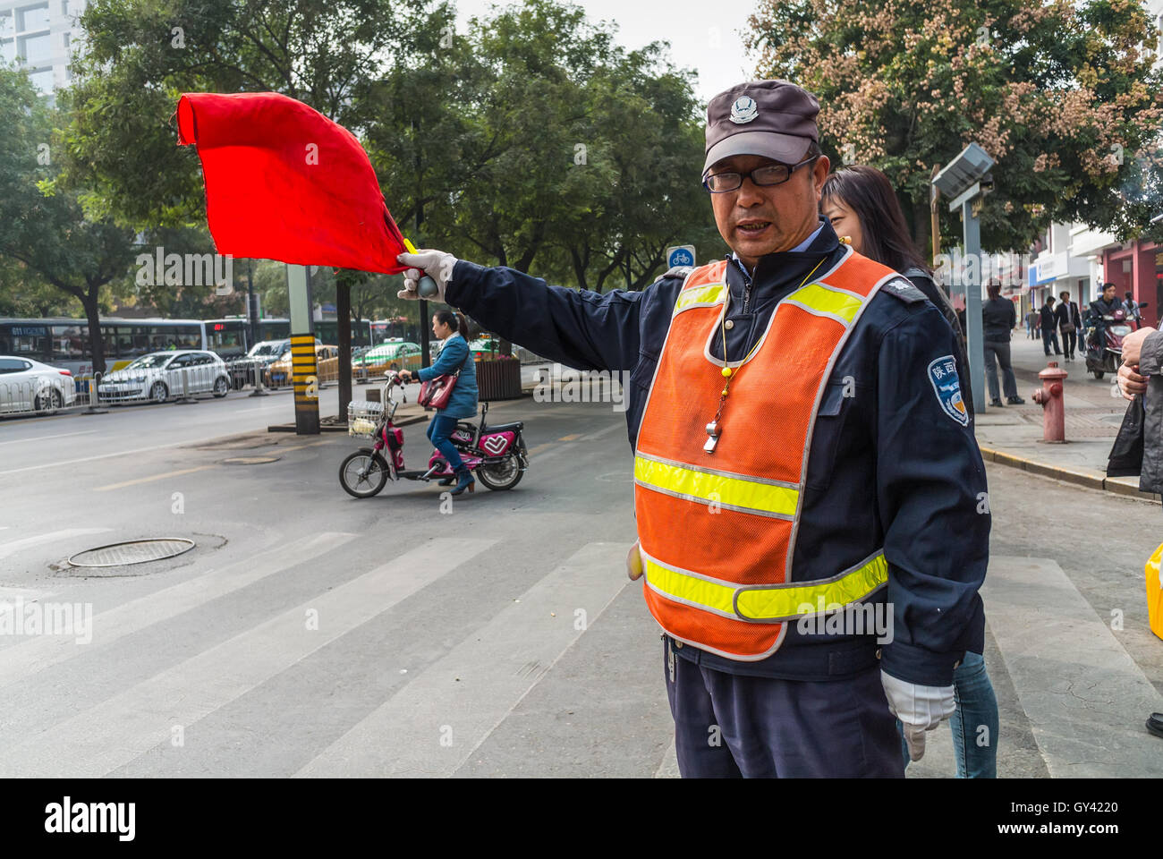 Chinese Traffic Warden is working at intersection in Xian, Shaanxi Province, China. - Stock Image