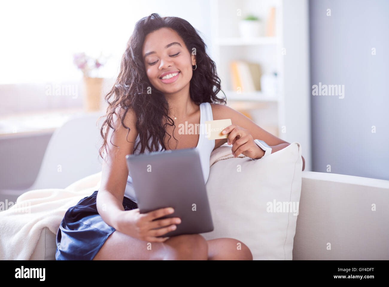 Cheerful woman using tablet - Stock Image