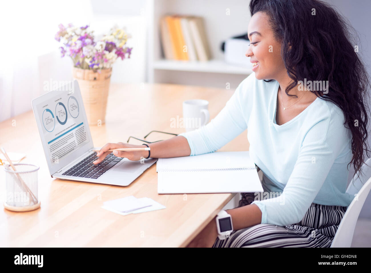 Positive woman using laptop - Stock Image